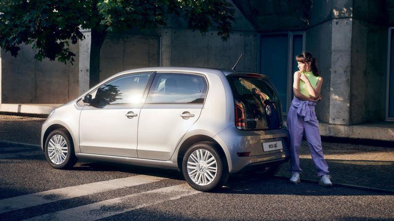 Ragazza in piedi vicino a eco up! Volkswagen in una via alberata