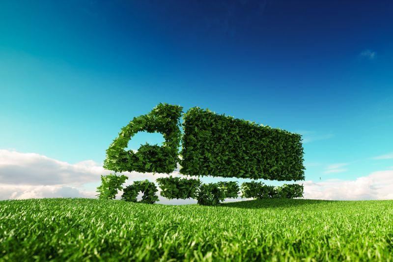 Ein Lkw aus grünen Blättern fährt über eine grüne Wiese. Das Bild symbolisiert umweltschonenden Güterverkehr.