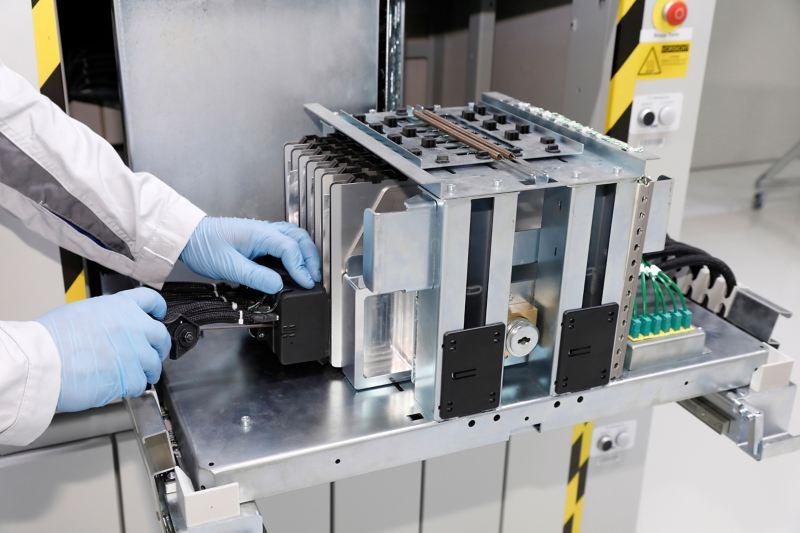 Ein Mitarbeiter mit Schutzhandschuhen schließt eine Batteriezelle zum ersten Mal an ein Ladekabel an.