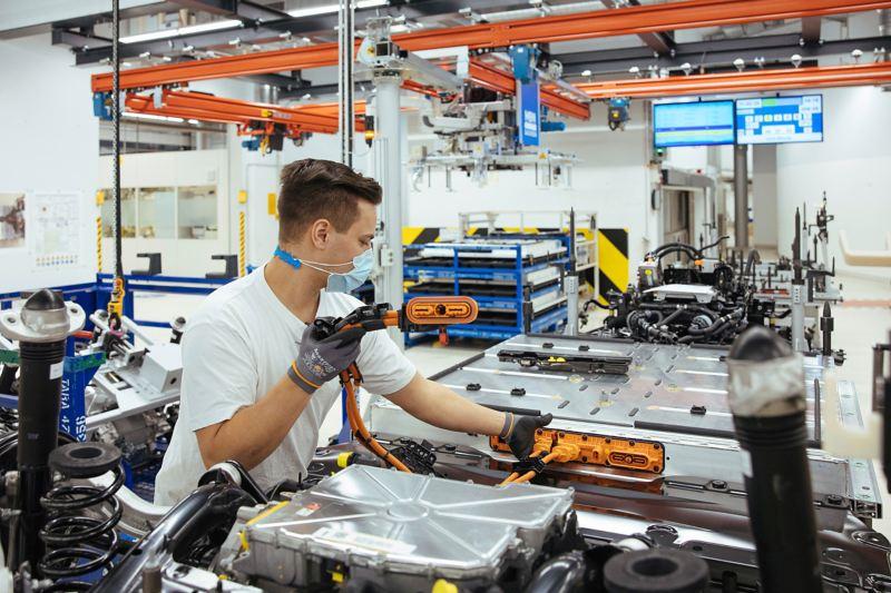 Ein Mitarbeiter überprüft ein Hochvolt-Kabel an einer Fahrzeugbatterie.