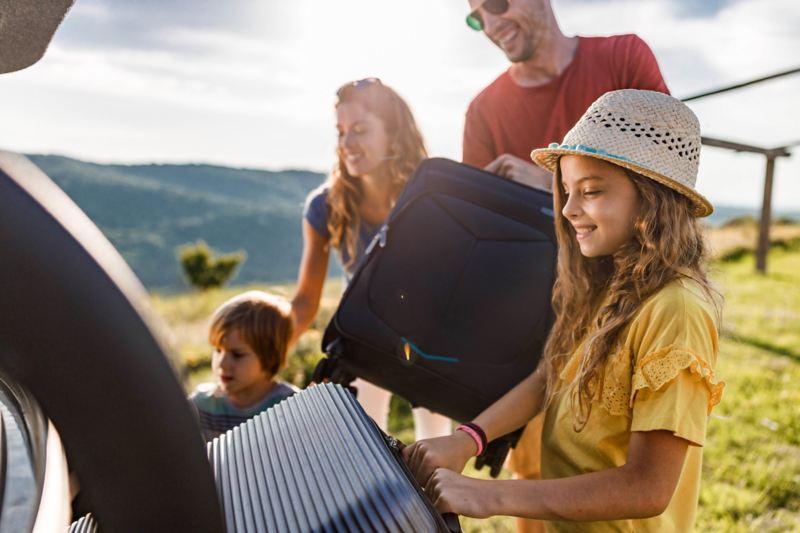 Eine Familie mit zwei Kindern holt ihre Koffer aus dem Kofferraum eines Autos, das bei schönem Wetter auf einer grünen Wiese in den Bergen geparkt ist.