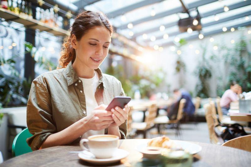 Eine junge Frau schaut im Café auf ihr Smartphone