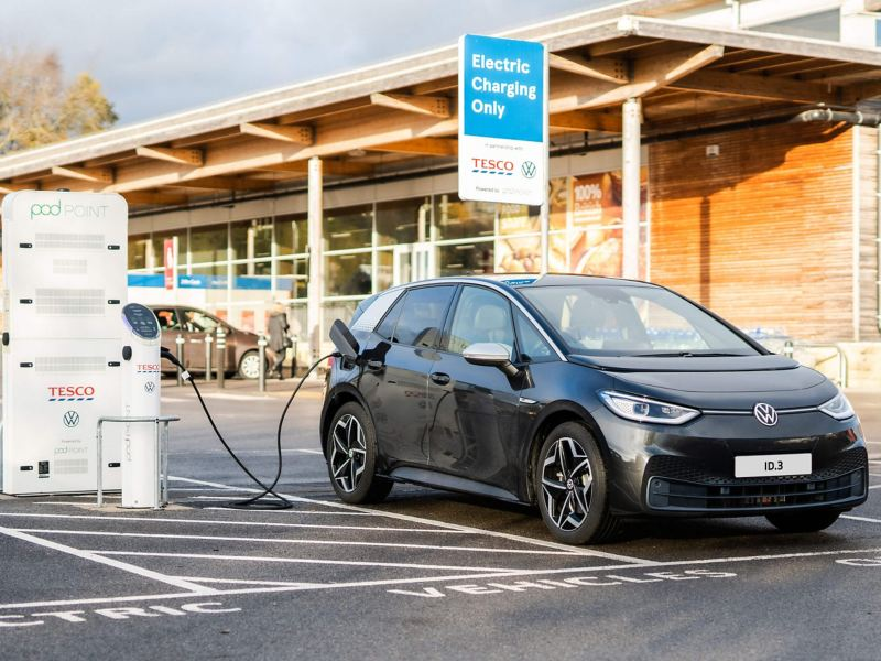 A Volkswagen ID.3 electric car parked at a Tesco store charging at a Tesco VW pod point