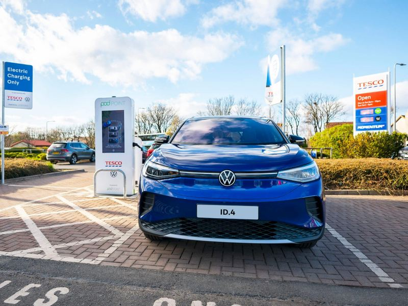 A Volkswagen ID.4 electric car parked at a Tesco store charging at a Tesco VW pod point