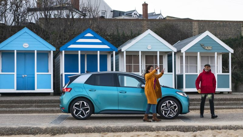 An ID.3 parked in front of beach huts at the seaside with a woman and man standing next to the car