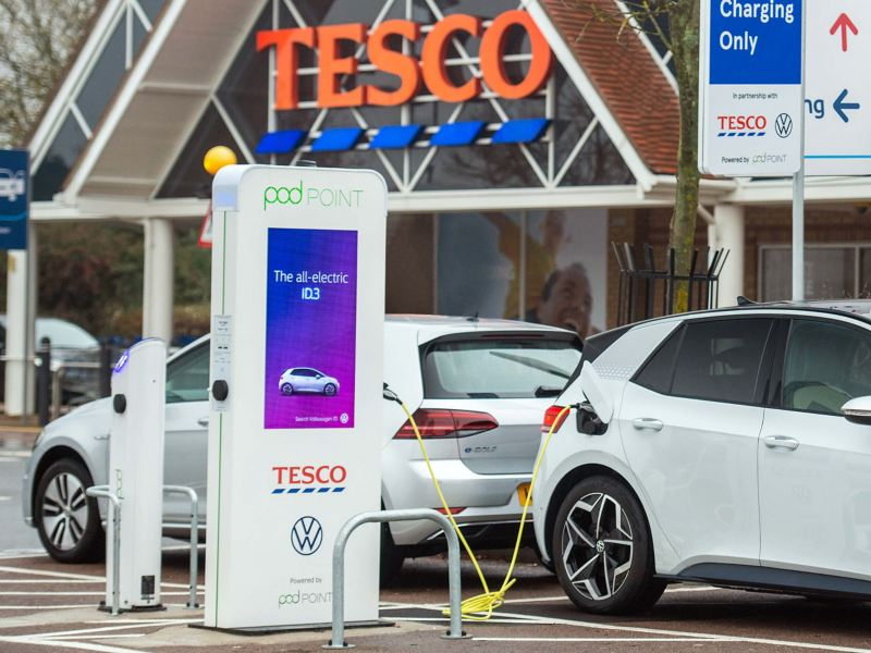 A Volkswagen e-Golf and ID.3 charging at a podPoint in front of a TESCO