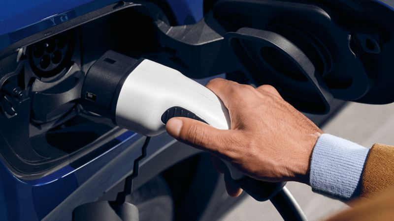 Closeup of someone charging an electric vehicle