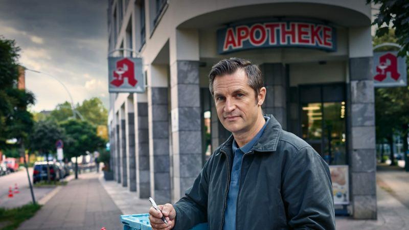Ein Mann mit Clipboard steht vor einer Apotheke.