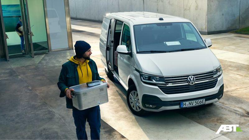Ein Mann trägt eine Kiste aus einem weißen VW Transporter Kombi.