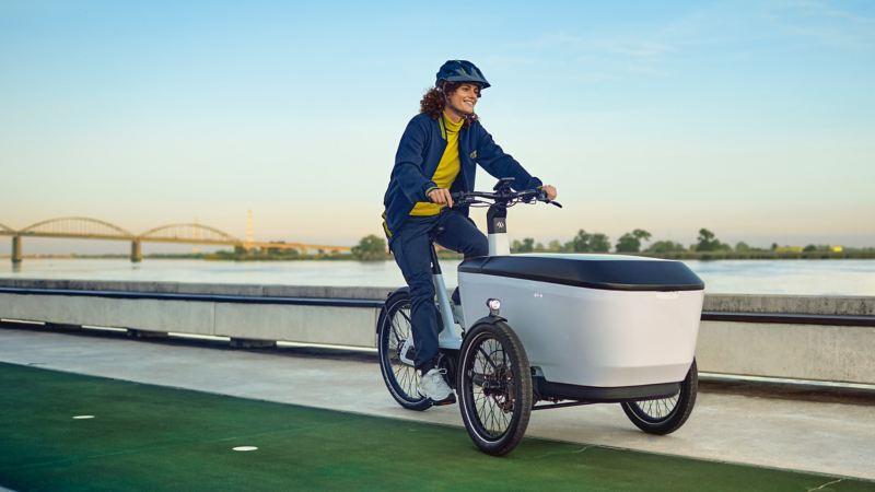 Bildet viser Volkswagen eCargo elsykkel og en kvinne som sykler på denne langs en elv i en by