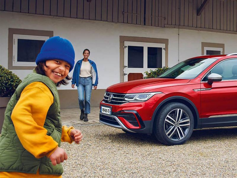 Enfant souriant devant un Nouveau Tiguan Allspace Volkswagen garer sur une maison