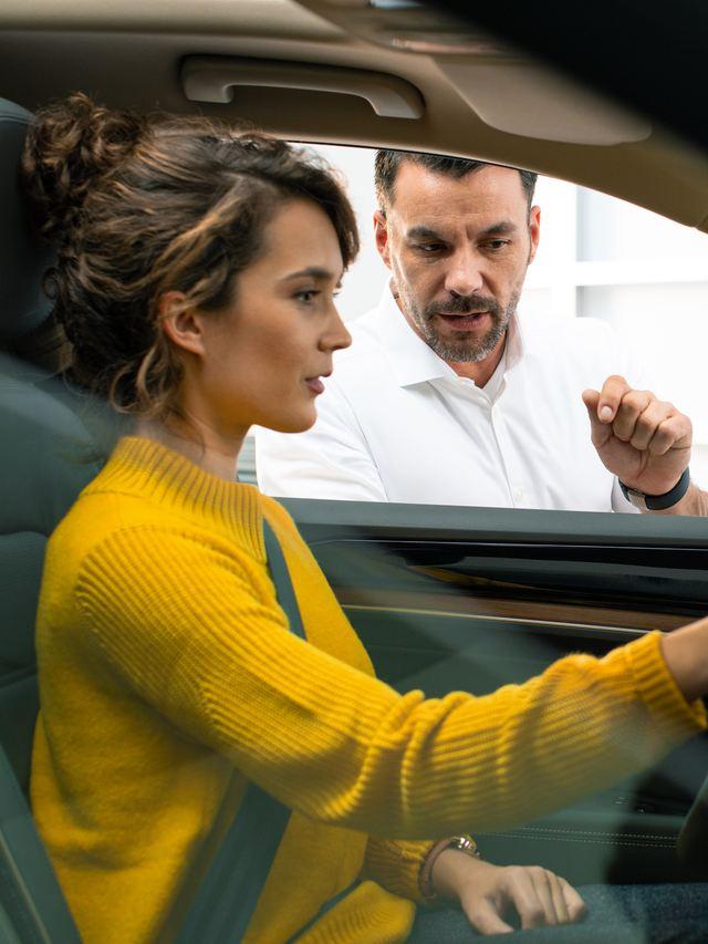 Deux hommes vérifient un document, lien vers la page « Services financiers » de VW