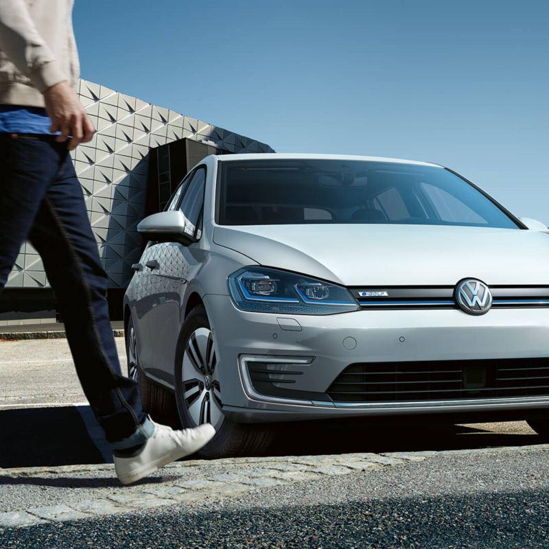Un passant devant une voiture Volkswagen