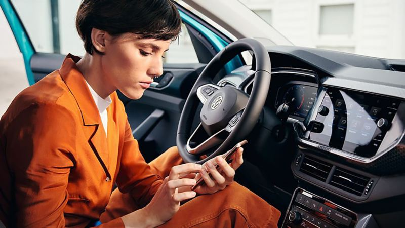A lady using her smartphone in a T-Cross