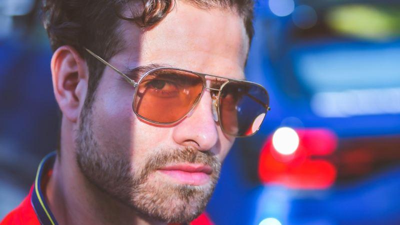 Hombre joven con lentes de sol y, de fondo, la parte trasera de un SUVW.