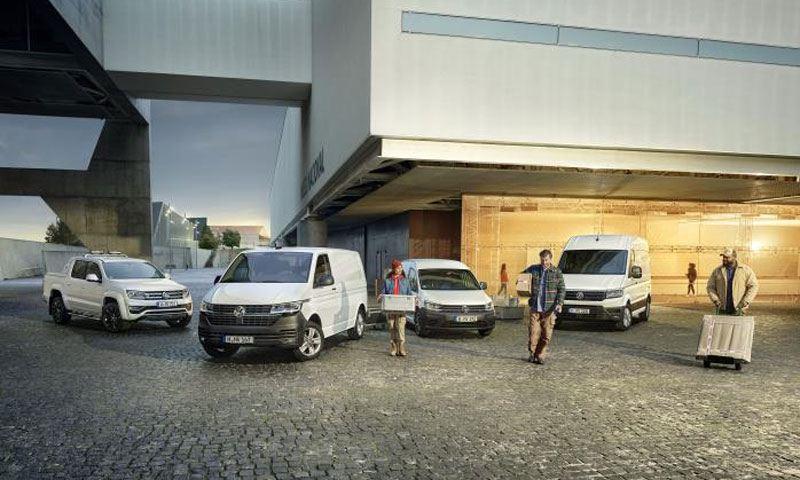 Tre lavoratori si allontanano con alcuni pacchi da quattro veicoli commerciali Volkswagen: Amarok, Transporter Furgone, Nuovo Caddy Cargo e Crafter Furgone.