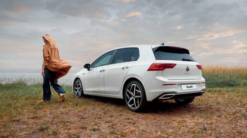 Una ragazza si allontana da una Volkswagen Golf 8 eTSI, vista posteriormente e parcheggiata in uno spiazzo erboso.