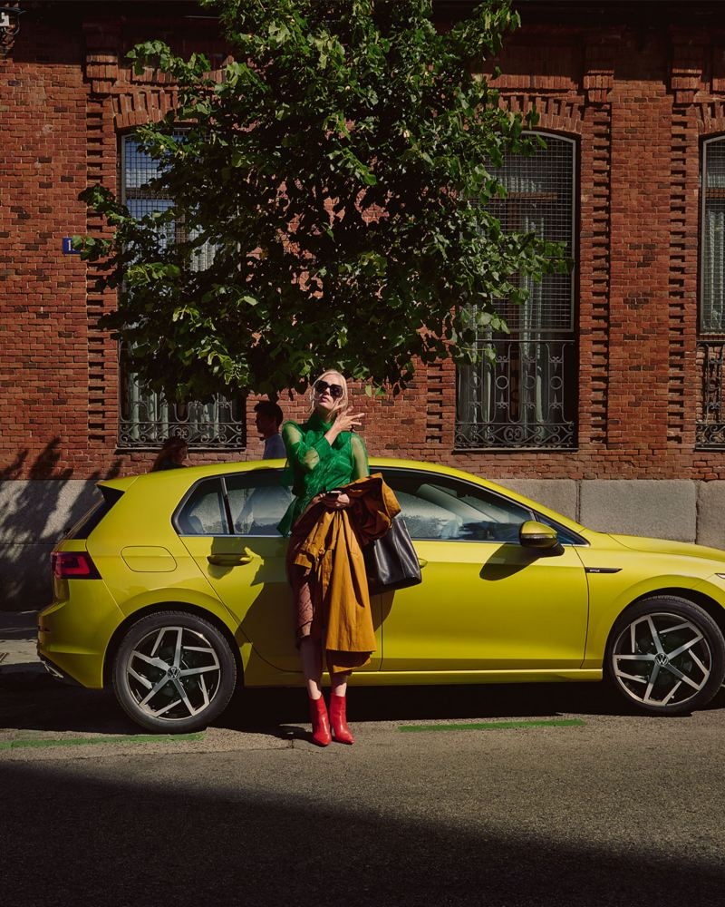 Nouvelle Golf eHybrid jaune devant un arbre et une maison avec une femme appuyée sur la voiture