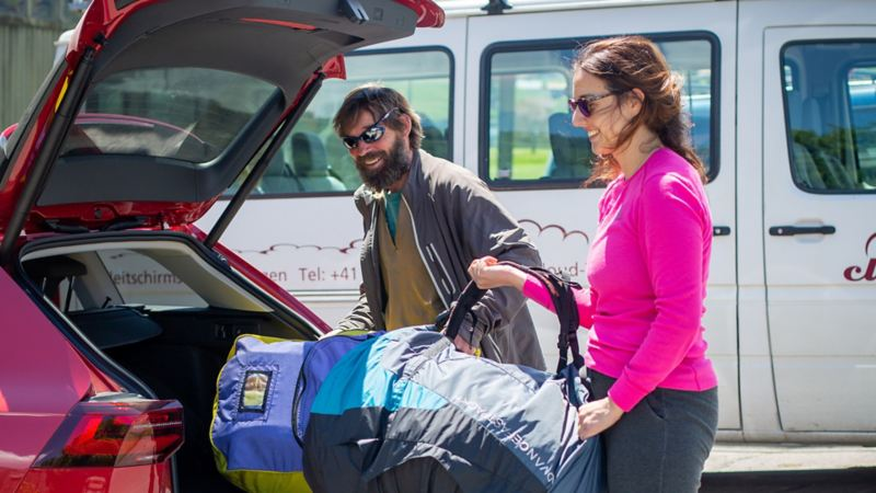 Marito e moglie mettono gli zaini nel bagagliaio della Golf Alltrack.