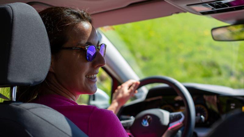 Una donna con gli occhiali da sole siede al volante della Golf Alltrack.