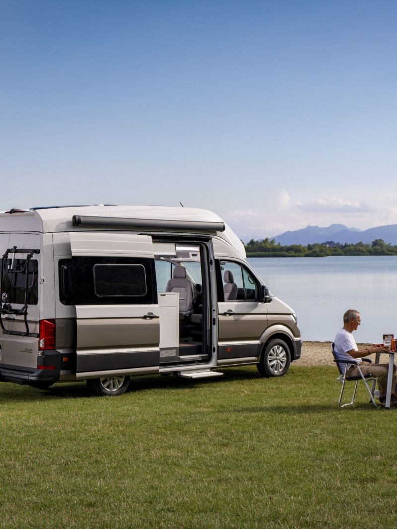 Volkswagen Grand California i para przy stoliku nad jeziorem