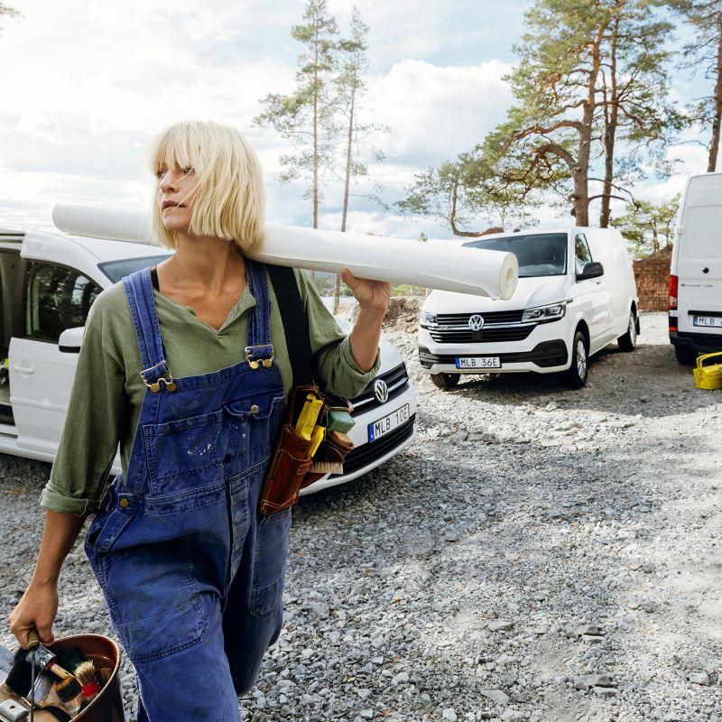 Hantverkare kvinna framför Volkswagen transportbilar