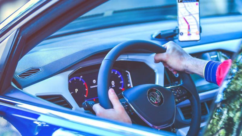 Hombre con manos sobre volante de auto Volkswagen equipado con sistemas de seguridad para evitar accidentes ji
