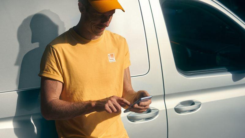 A man using an phone next to a VW van.