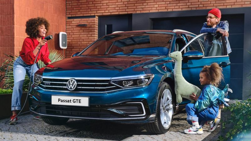 A young couple plays with their little daughter around the VW Passat GTE Estate parked in the driveway.