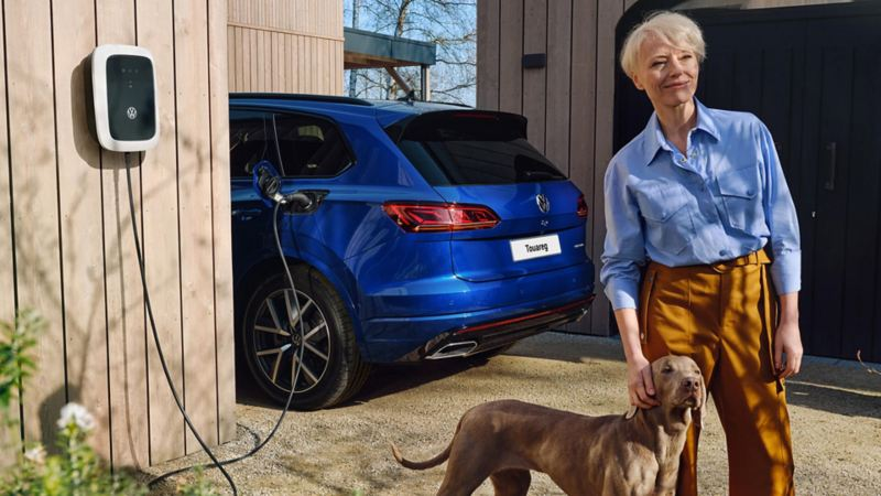 A woman stands with her dog in front of a loading VW Touareg eHybrid.