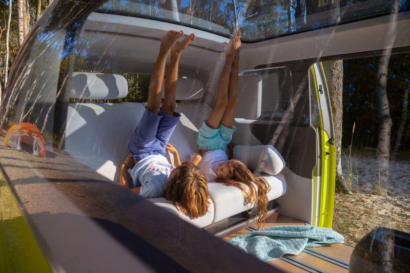 Un garçon et une fille font de la gymnastique à l'intérieur du Volkswagen ID. Buzz.