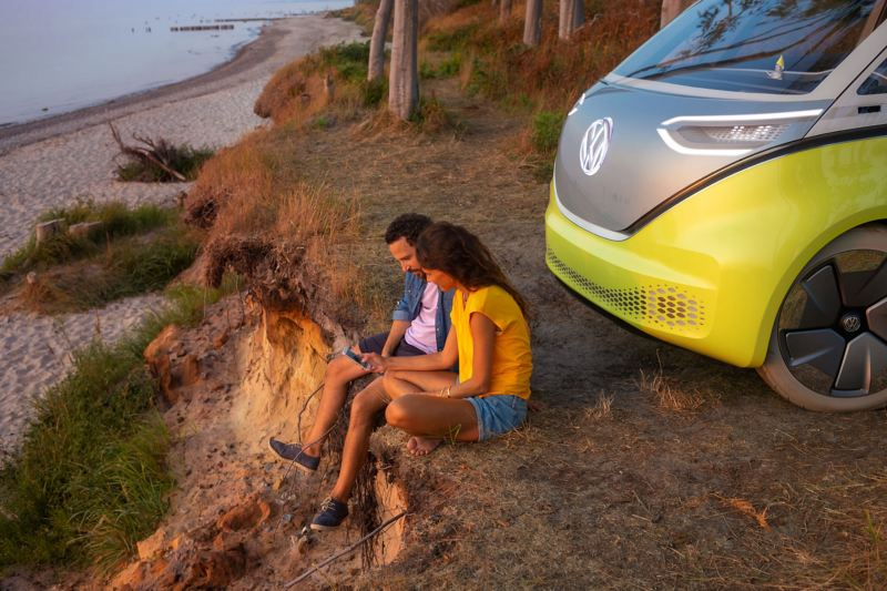Une femme et un homme sont assis devant le Volkswagen ID. Buzz sur une plage.