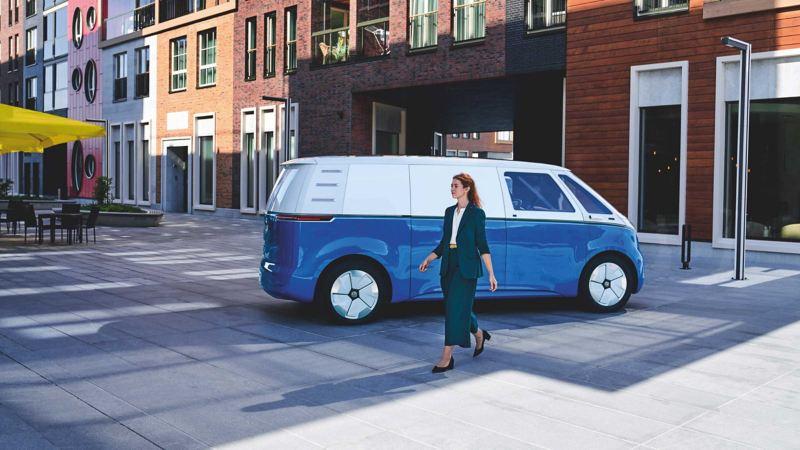 Bildet viser en hvit og blå Volkswagen ID. BUZZ Cargo elvarebil og en budbilsjåfør som løfter pakker inn i varerommet