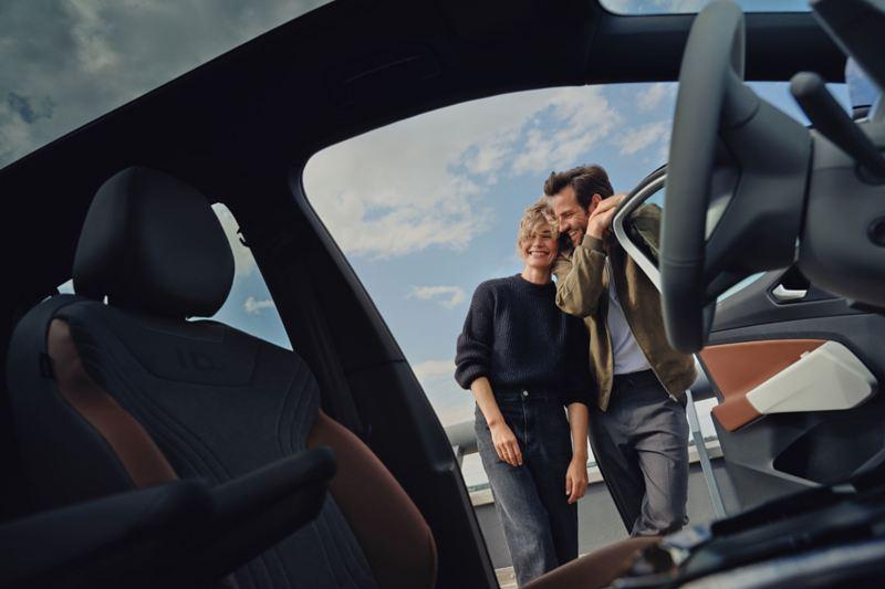 Un uomo e una donna aprono la portiera della loro Volkswagen ID.4 1st e ne osservano gli interni.