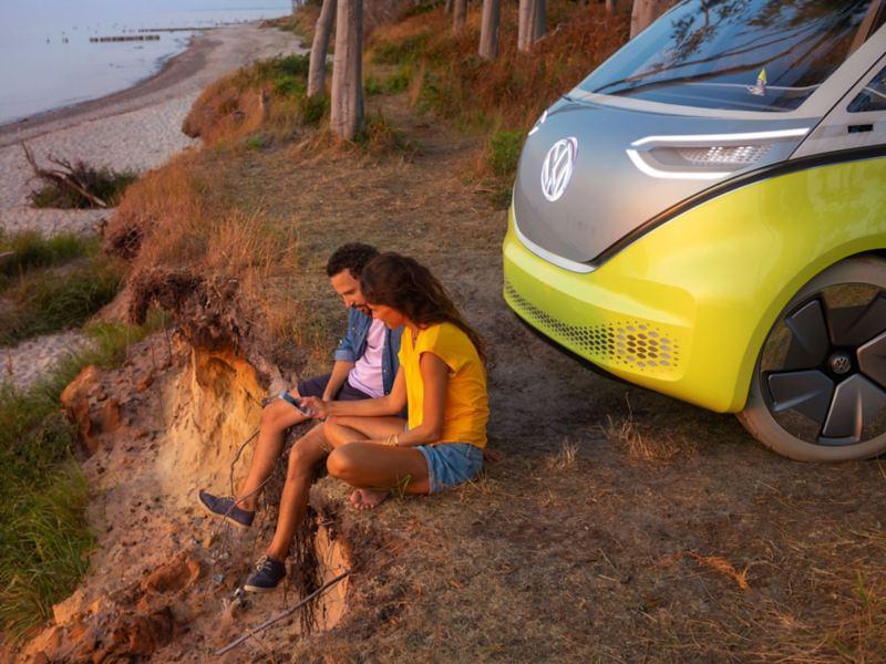 kvinna och man sitter framför konceptbilen ID. Buzz