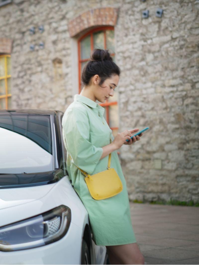 Kobieta opiera się o VW ID.3, podczas gdy samochód jest ładowany ze stacji IONITY