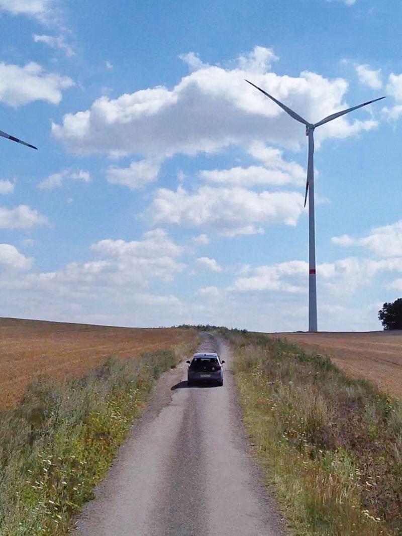 ID.3 fährt auf einen Feld weg und 3 Windmühle im Hintergrund