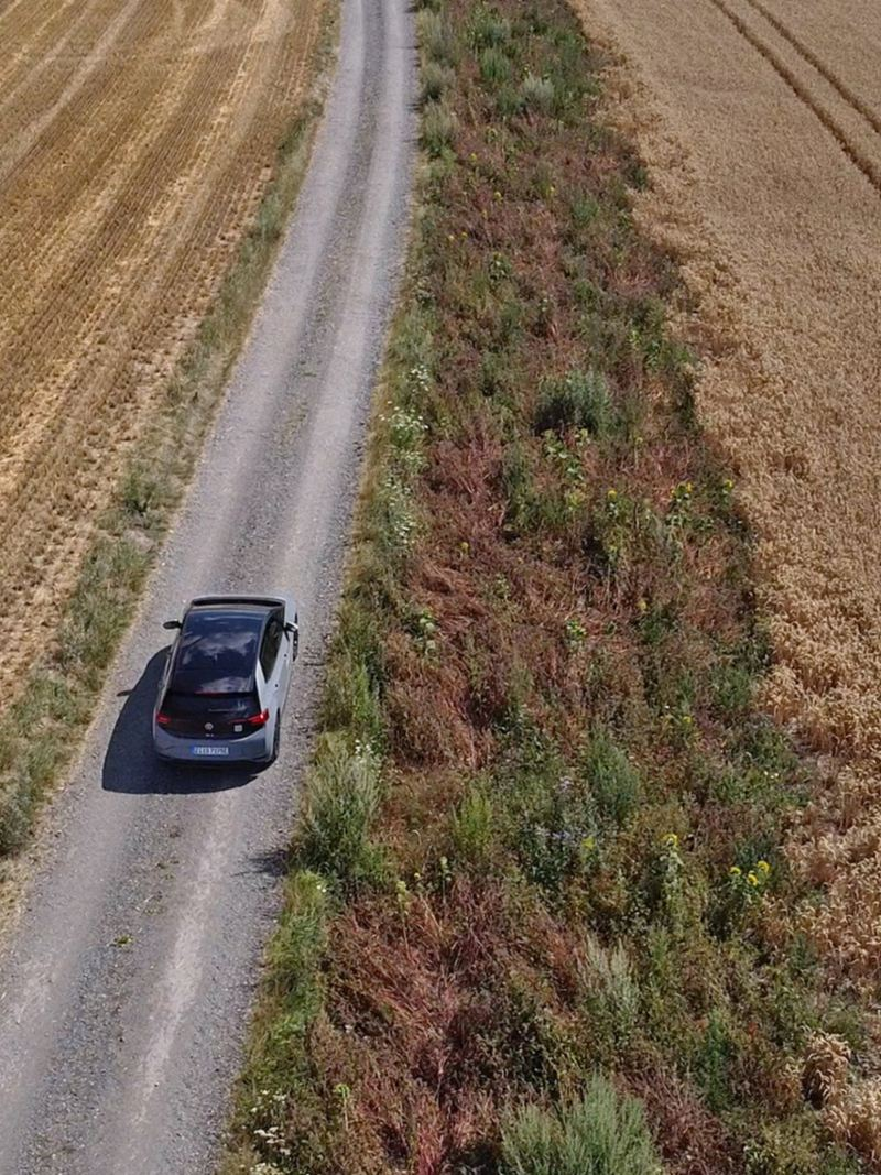 ID.3 fährt auf einen Weg zwischen Felder