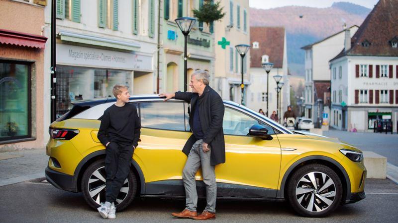Vater und Sohn lehnen sich an einen gelben ID.4