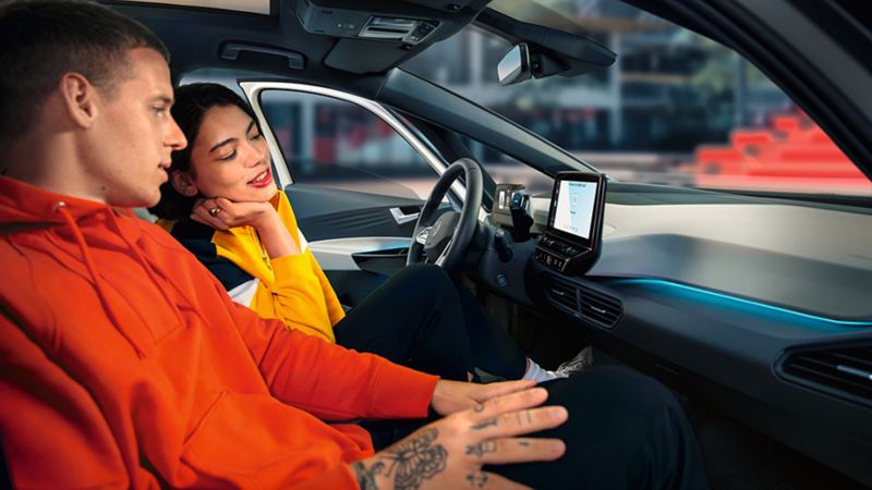 People in a Volkswagen car, looking at the central touchscreen using the EV Check app.
