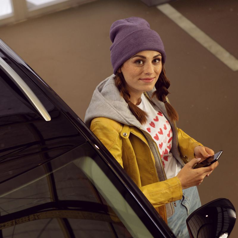 A woman leaning on a Volkswagen vehicle