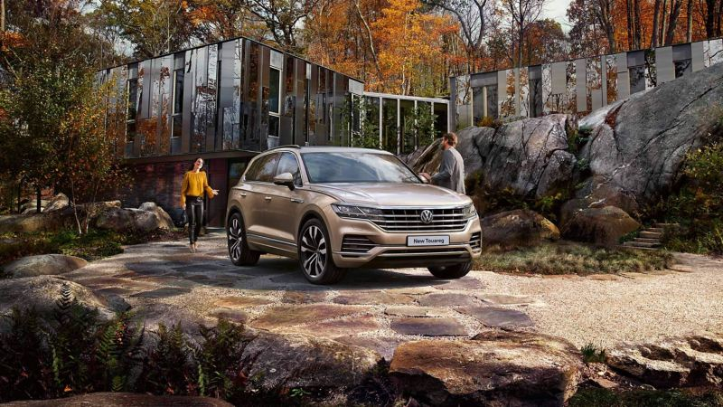 A couple standing near a parked Touareg