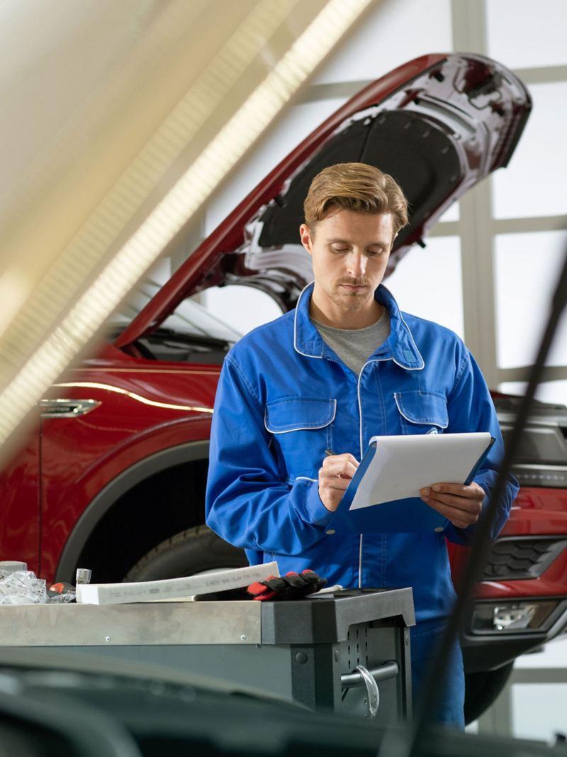Volkswagen service employee in front of a red Volkswagen