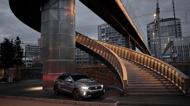 Nella luce della sera, il T-Roc R con luci parcheggiato accanto a una scala a chiocciola