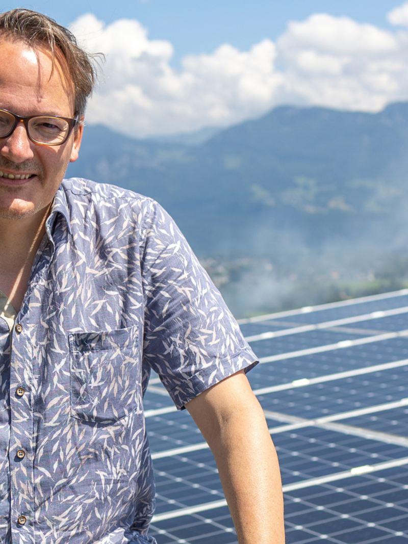 Christof Schmid debout sur le toit devant sa propre alimentation en énergie solaire.
