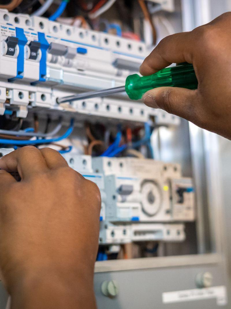 Un homme ajuste quelque chose sur le panneau électrique
