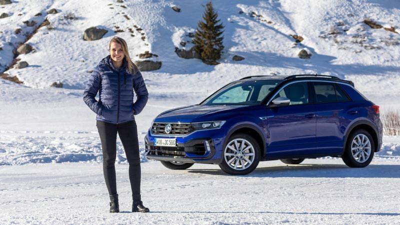 Rennfahrerin posiert vor blauen T-Roc R im Schnee.