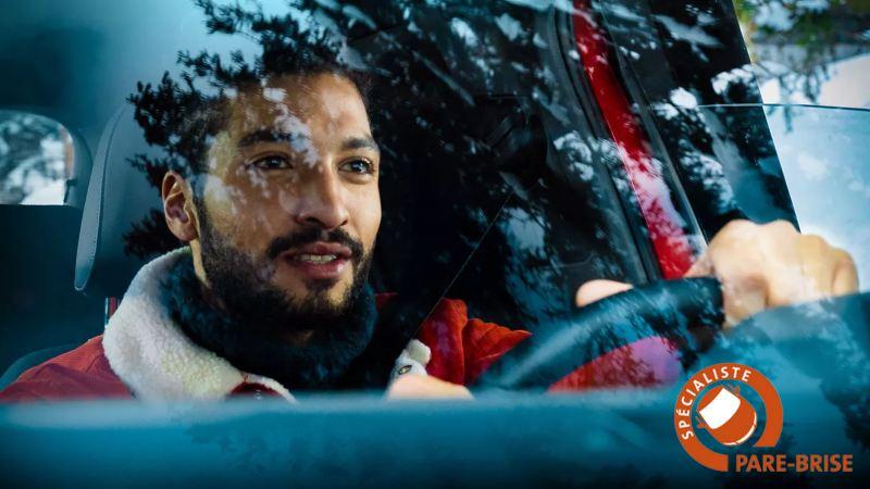 Un homme roule dans une Volkswagen rouge et regarde à travers le pare-brise