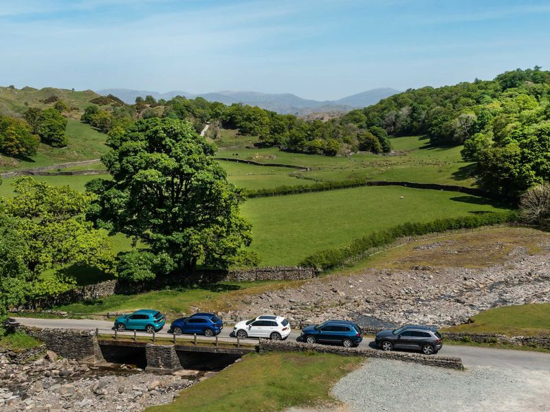 A shot of a range of VW cars on a country road