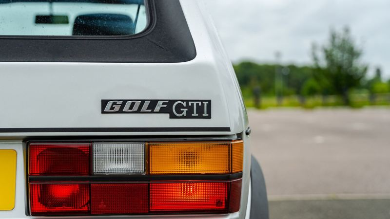 A rear shot of a silver Mk 1 VW Golf GTI focussed on the logo